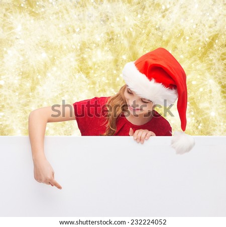 christmas, holidays and advertisement concept - happy girl in santa helper hat pointing finger on blank white board over yellow lights background
