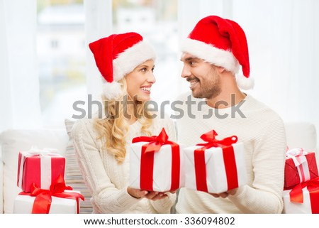 christmas, holidays and people concept - happy couple in santa hats exchanging gifts at home - stock photo