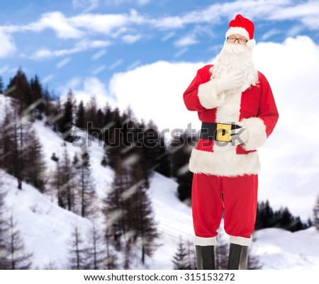 christmas, holidays and people concept - man in costume of santa claus over snowy mountains background