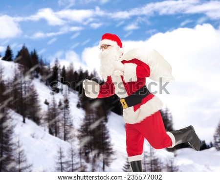 christmas, holidays and people concept - man in costume of santa claus running with bag over snowy mountains background - stock photo