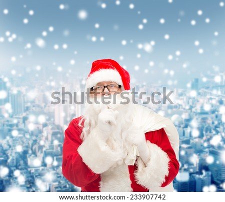 christmas, holidays and people concept - man in costume of santa claus with bag making hush gesture over snowy city background - stock photo