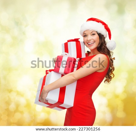 christmas, holidays, celebration and people concept - smiling woman in red dress with gift boxes over yellow lights background