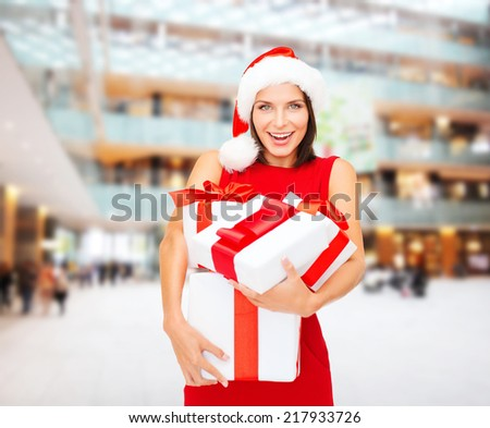 christmas, holidays, celebration and people concept - smiling woman in santa helper hat and red dress with gift boxes over shopping center background - stock photo