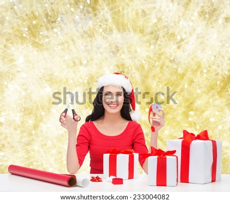 christmas, holidays, celebration, decoration and people concept - smiling woman in santa helper hat with scissors packing gift boxes over yellow lights background - stock photo