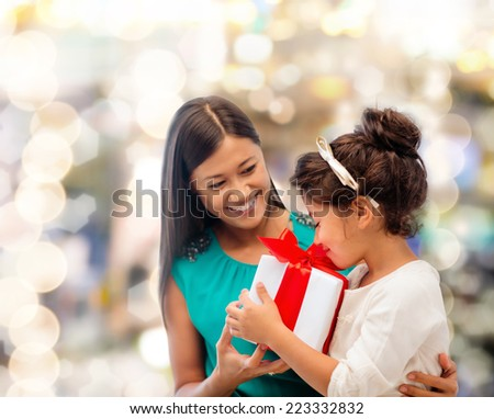 christmas, holidays, celebration, family and people concept - happy mother and little girl with gift box over lights background - stock photo