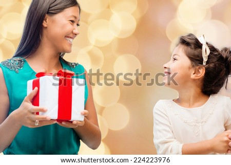 christmas, holidays, celebration, family and people concept - happy mother and little girl with gift box over beige lights background - stock photo