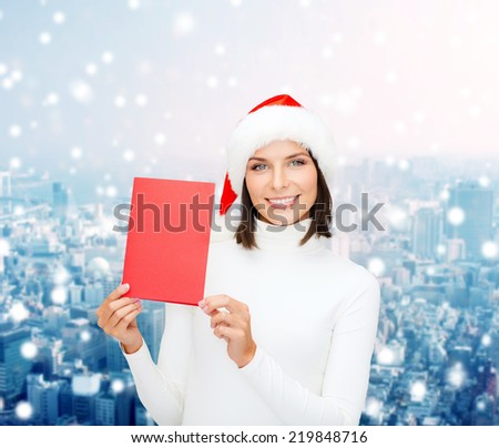 christmas, holidays, celebration, greeting and people concept - smiling woman in santa helper hat with greeting card over snowy city background - stock photo