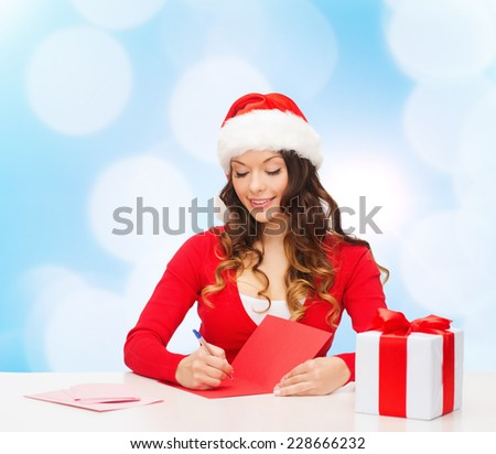 christmas, holidays, celebration, greeting and people concept - smiling woman in santa helper hat with gift box writing letter or sending post card over blue lights background - stock photo