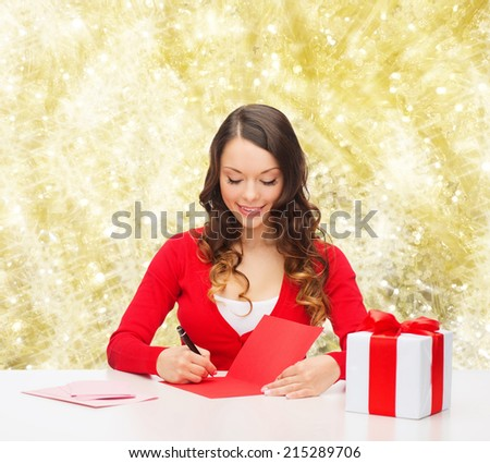 christmas, holidays, celebration, greeting and people concept - smiling woman with gift box writing letter or sending post card over yellow lights background - stock photo