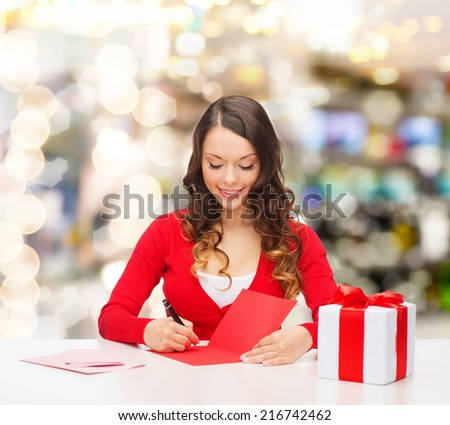 christmas, holidays, celebration, greeting and people concept - smiling woman with gift box writing letter or sending post card over lights background - stock photo