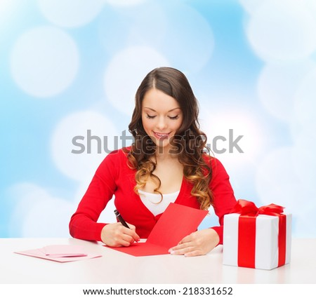 christmas, holidays, celebration, greeting and people concept - smiling woman with gift box writing letter or sending post card over blue lights background - stock photo