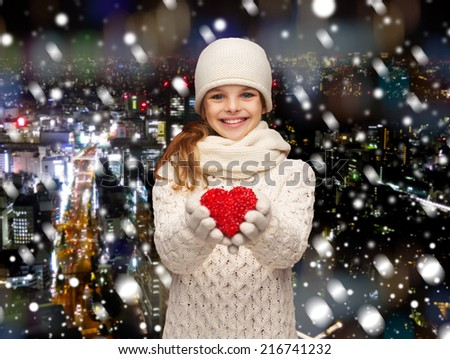 christmas, holidays, childhood, presents and people concept - dreaming girl in winter clothes with red heart over snowy night city background - stock photo