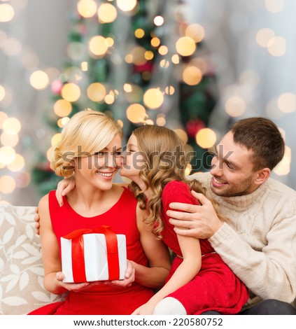 christmas, holidays, family and people concept - happy mother, father and little girl with gift box kissing over living room and christmas tree background - stock photo