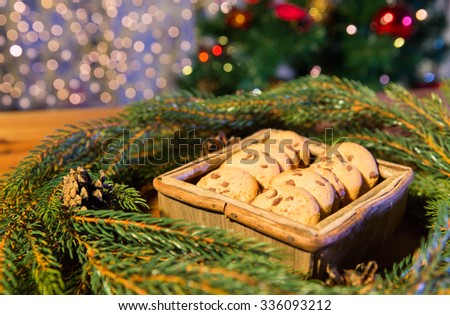 christmas, holidays, food and baking concept - close up of natural green fir christmas wreath and oat cookies in wooden box on table over lights - stock photo