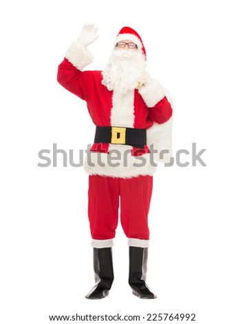 christmas, holidays, gesture and people concept - man in costume of santa claus with bag waving hand - stock photo
