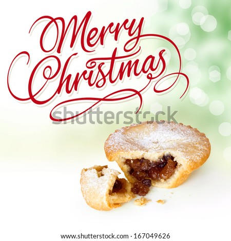 Christmas Holidays Greeting Card. Merry Christmas calligraphic type lettering with Mince Pie Broken Open on Christmas Tree background with bokeh lights - stock photo