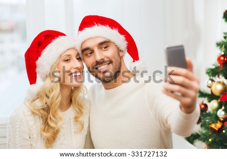 christmas, holidays, technology and people concept - happy couple in santa hats taking selfie picture with smartphone at home