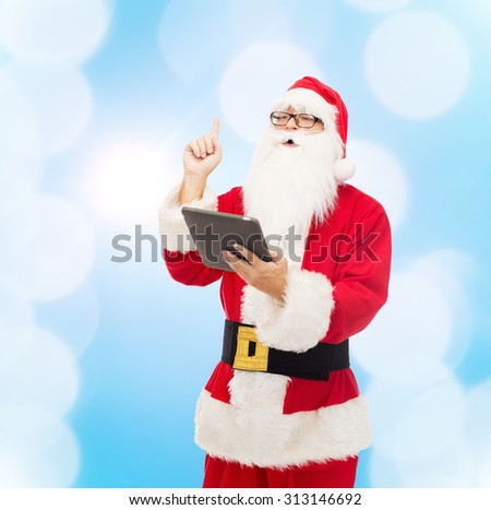 christmas, holidays, technology and people concept - man in costume of santa claus with tablet pc computer pointing finger up over blue lights background - stock photo