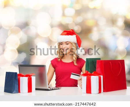 christmas, holidays, technology and shopping concept - smiling woman in santa helper hat with gifts, credit card and laptop computer over lights background - stock photo