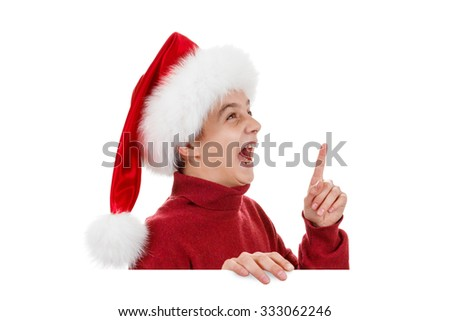 Christmas holidays, the concept of advertising Xmas - happy teen boy in Santa hat pointing finger on white board. Object isolated on white background - stock photo