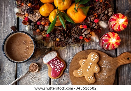 Christmas homemade gingerbread cookies, hot chocolate and candles on wooden table - stock photo