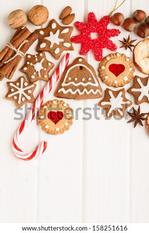 Christmas homemade gingerbread cookies,spice and decoration over white wooden board