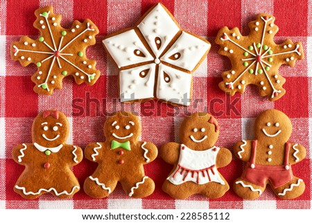 Christmas homemade gingerbread couples on tablecloth - stock photo