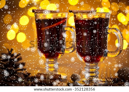 Christmas hot mulled wine with spices on a wooden table with stars and snow. The idea for creating greeting cards