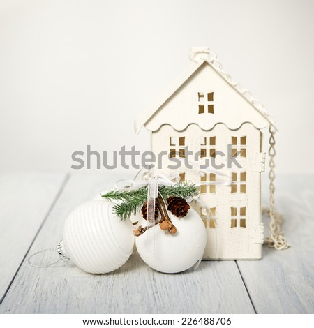 Christmas house and balls on a white wooden background, selective focus - stock photo