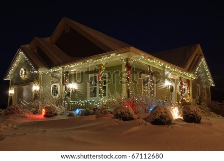 Christmas House decorated with lights at night in Winter - stock photo