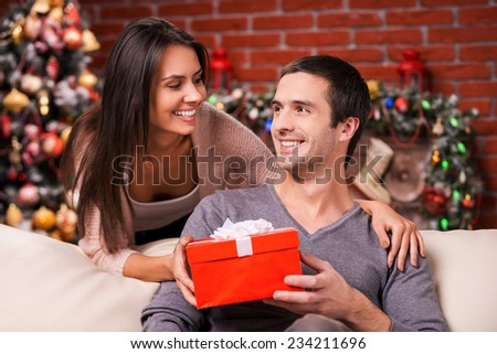 Christmas is time for giving. Beautiful young woman giving a red gift box to her boyfriend and smiling with Christmas Tree in the background  - stock photo