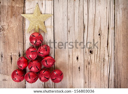 Christmas jingle bells and golden star shaped like a Christmas tree on a rustic wooden plank - stock photo