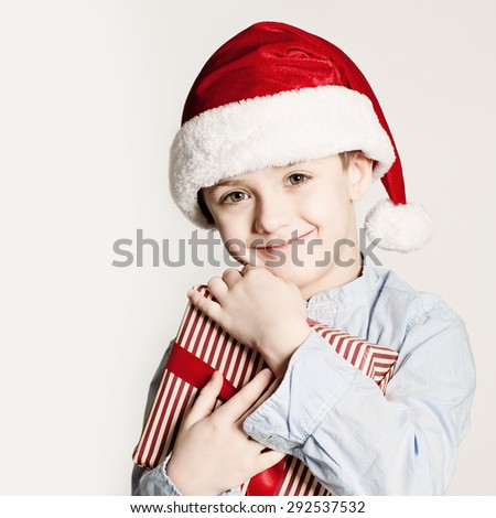 Christmas Kid with Xmas Gift Box. Child Boy with Red Santa Hat and Gift. - stock photo