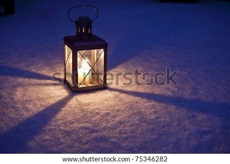 Christmas Lantern A candle lit inside a lantern sitting on the snow in the dark - stock photo
