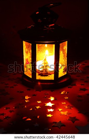 Christmas lantern glowing in dark with silver stars on red background - stock photo