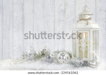 Christmas lantern with ornaments and pine cones in snow with texture overlay - stock photo