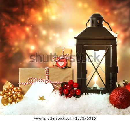 Christmas lantern with presents, ornaments and snow on a orange shinning night background - stock photo