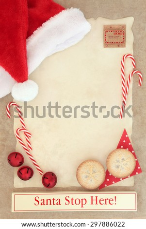 Christmas letter to santa claus with stop here sign on parchment paper with mince pies and decorations over brown paper background. - stock photo