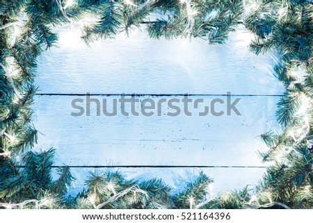 Christmas light blue wooden background with lightbulb and spruce branches