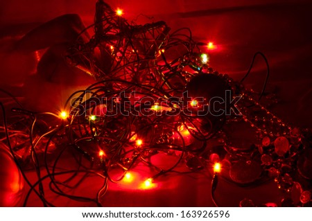 Christmas lights and decorations in the evening on a red backgro