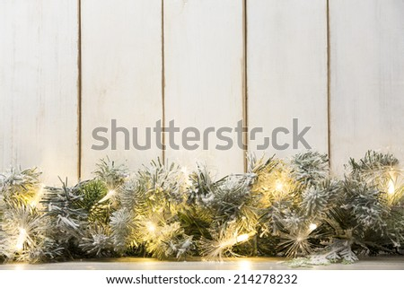 Christmas lights and fir branch on wood plank - stock photo
