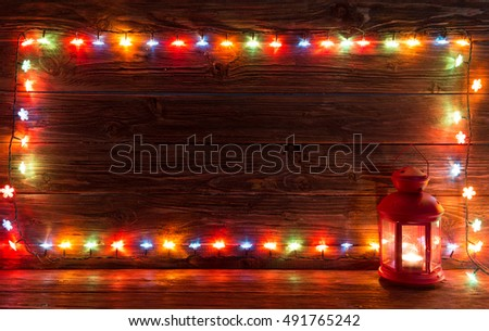 Christmas lights and vintage lantern on wooden background. Frame of lights. Merry Christmas. Christmas. Happy Christmas. Christmas background. Christmas light.