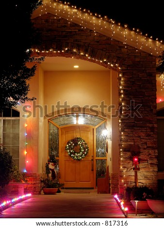 Christmas lights at entry - brick entry with wreath, lights, and snowman. - stock photo