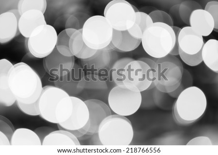 Christmas Lights Black and White Bokeh - A black and white bokeh background created by a set of defocused Christmas lights. - stock photo