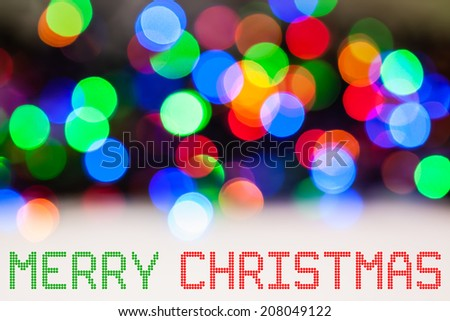 Christmas Lights Color Bokeh - A bright multicolor bokeh background created by a set of defocused Christmas lights with a round pixel Christmas message. - stock photo