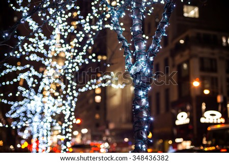 christmas lights hanging in a tree in the city. - stock photo
