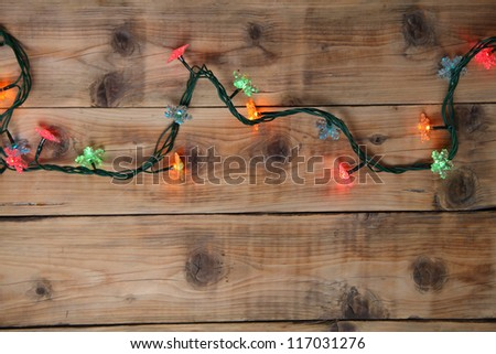 Christmas lights on a wooden background with copy space. Decorative garland - stock photo