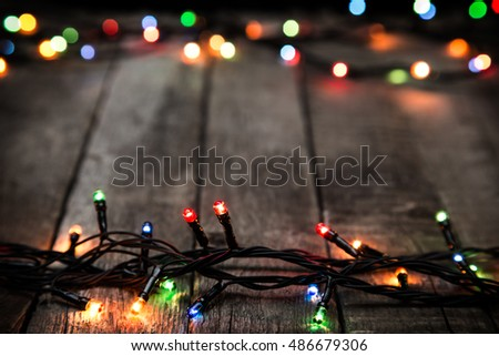 Christmas lights on dark wooden rough background, abstract template with selective focus