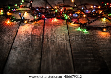 Christmas lights on dark wooden rough background, empty space for text