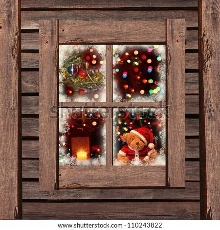 Christmas  lights seen through a wooden cabin window - stock photo